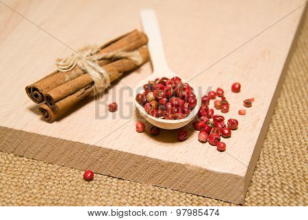 Spoon With A Mixture Of Grains Of Pepper And Cinnamon On A Wooden Surface