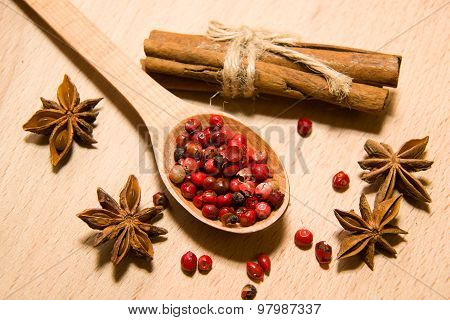 Spoon With A Mixture Of Grains Of Pepper, Cinnamon And Star Anise On A Wooden Surface