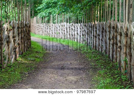 Defocused Background Of Turning Footpath Between Decorative Wooden Fences