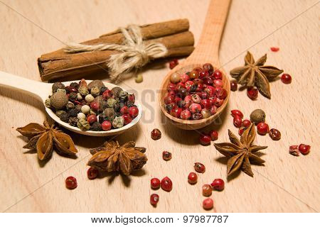 Spoons With A Mixture Of Grains Of Pepper, Cinnamon And Star Anise On A Wooden Surface