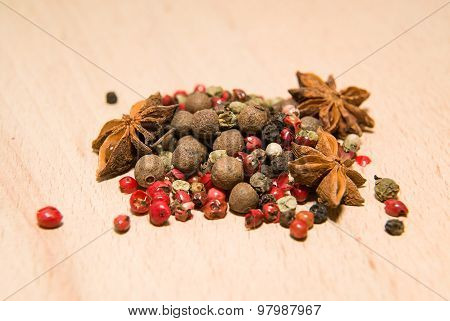 A Mixture Of Grains Of Pepper And Star Anise On A Wooden Surface