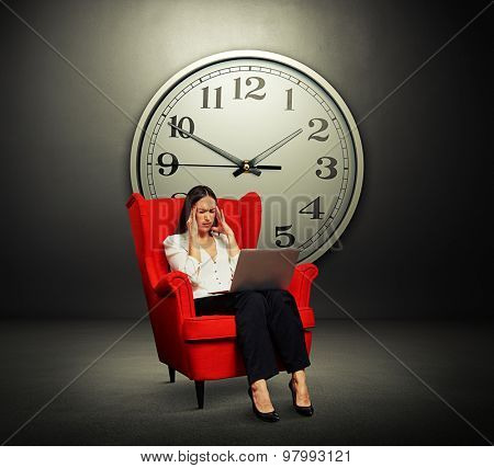 tired woman with laptop sitting on the red chair over grey wall with big clock