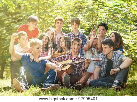 Groupe Of Happy Young People Singing With Guitar Together