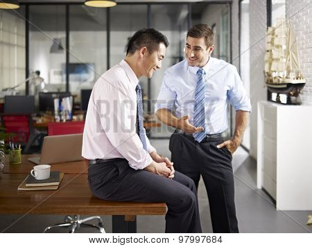 Asian And Caucasian Colleagues Talking In Office