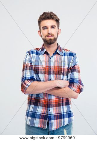 Portrait of a handsome young man standing with arms folded isolated on a white background. Looking at camera