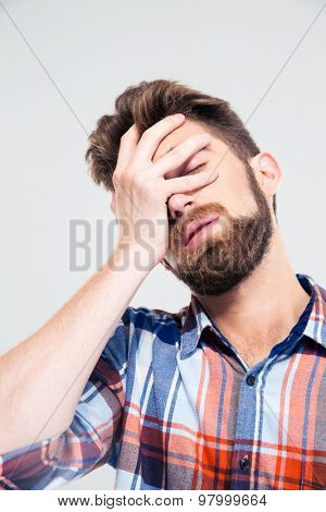 Portrait of sad man covering his face with hand isolated on a white background