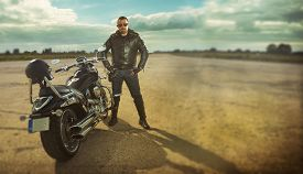 pic of biker  - Biker in leather jacket standing by a motorcycle.
