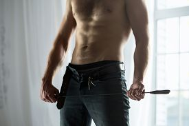 foto of bondage  - Cropped hands of topless guy with jeans unbuttoned playfully holding a whip BDSM - JPG