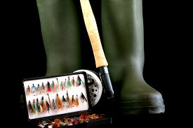 picture of fly rod  - Fly fishing rod and reel with green wading boots and fishing flies in flybox on black background - JPG