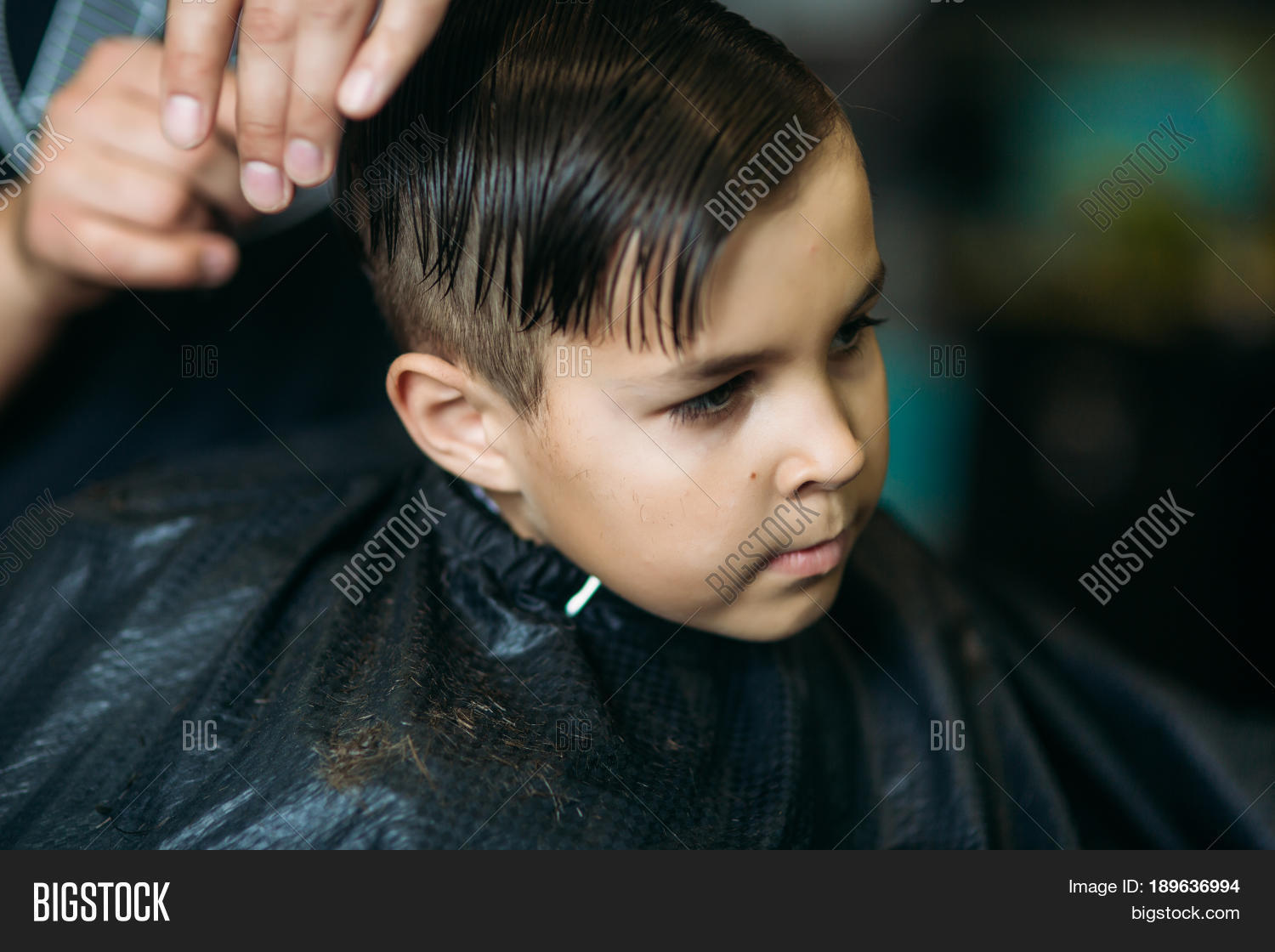 Little Boy Getting Haircut By Barber While Sitting In Chair At Barbershop On