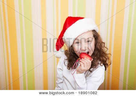 beautiful little girl bites a red heart wearing santa claus red hat