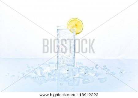 advertising still-life with glass of soda and lemon in ice over white background. freshness.