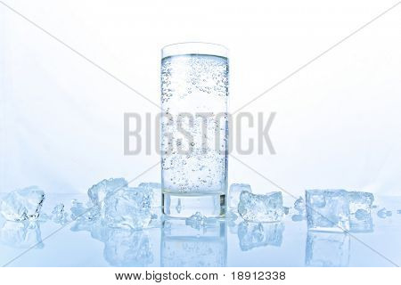 advertising still-life with glass of soda with ice over white background. freshness.