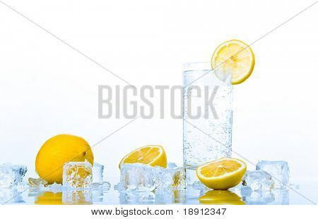 advertising still-life with glass of soda and lemons in ice over white background. freshness.