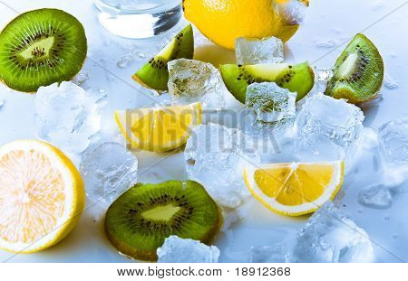 advertising still-life with glass of soda and lemons and kiwi in ice over white background. freshness.