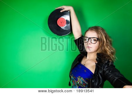 fashion shot of a young woman holding a red vinil disc in hands over green background