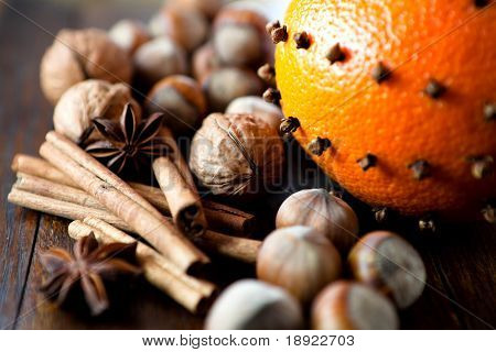 Orange with cloves and nuts on rustic background
