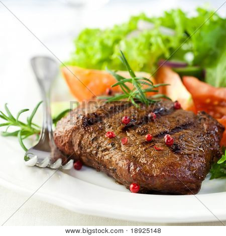 Closeup of grilled steak with pepercorns and rosemary