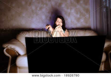 scarred beautiful girl watching TV on a couch
