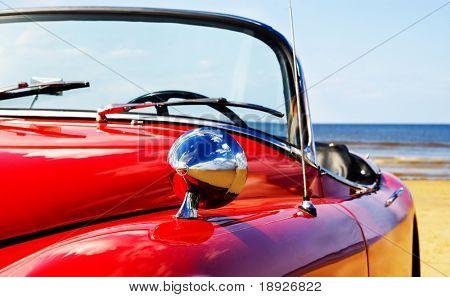 Old classic red jaguar at beach