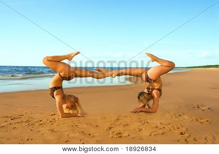 Two acrobatic girl on the beach