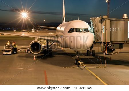 plane parked at the airport at night