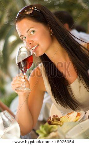 Mujer joven hermosa cata de vino tinto en el restaurante (dof superficial)