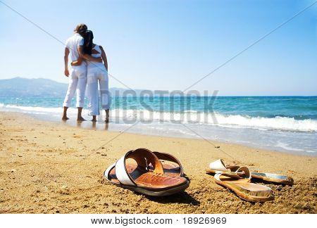Pareja joven atractiva en la playa (vista frontal centrado)