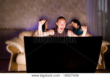 Three friends are watching TV