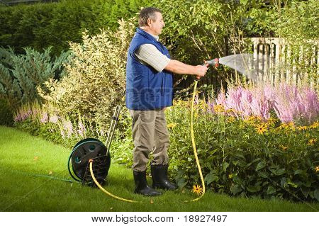 Senior man watering flowers in the garden
