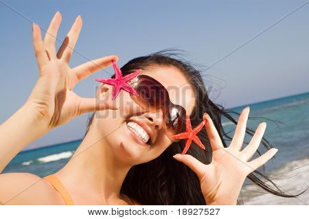 oung beautiful woman holding two starfish at the seaside