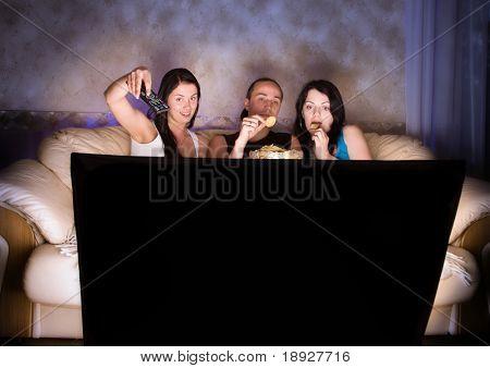 Três amigos estão assistindo TV