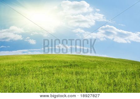 Green hill under blue cloudy sky whit sun