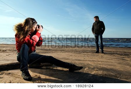 Young woman taking a photo of her boyfriend on the beach (Woman in focus)
