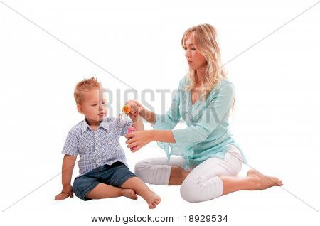 Portrait of happy mother with joyful son playing with soap bubbles