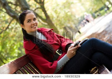 Young Caucasian woman with a cell phone, sitting in a park on a wooden bench, reading a SMS.