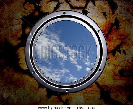 Round window in prison, cloudy sky