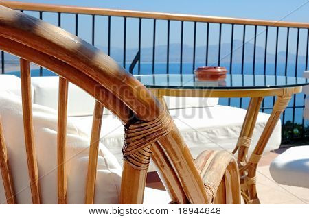 Back of chair and glass table in the bar of a luxury hotel, bright sun, see view in background