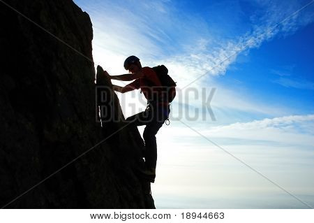 Rock climber silhouette, partial cloudy sky, horizontal orientation