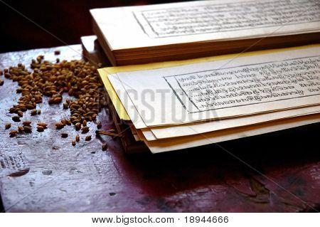 Cerca de la foto de un libro de oración tibetano tradicional, con la semilla del grano utilizado durante la religión rit