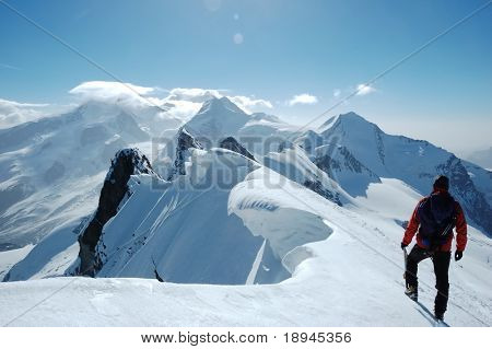 Lonely climber, on background the peaks and glaciers of Monte Rosa massif, west Alps, Europe