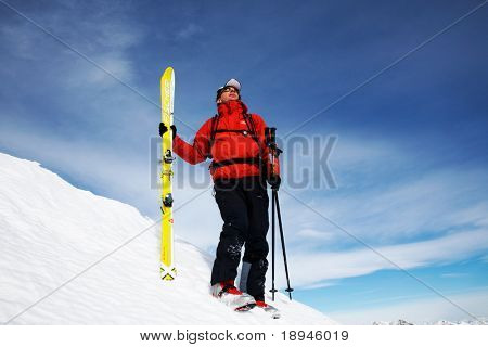 A lone skier on the top of a snowy mountain; horizontal frame. Italian alps.