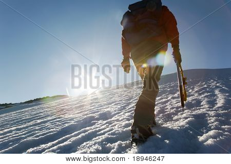 Climber walking on a glacier at sunset