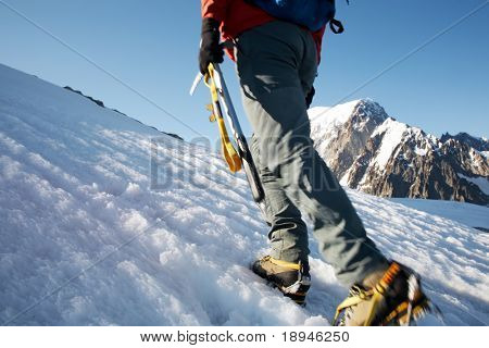 Climber walking on a glacier at sunset, in background the south side of Mont Blanc, Italy- France
