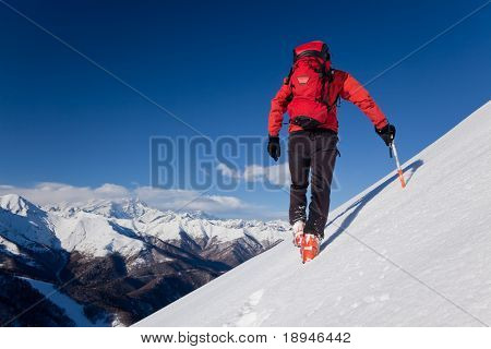 A male climber , dressed in red, climbs down a snowy slope. Winter clear sky day. In background the Monte Rosa massif, Italy, Europe.