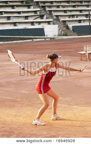 blond girl playing tennis at open court