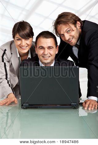 tres personas de negocio feliz detrás de un ordenador portátil, mirando a cámara