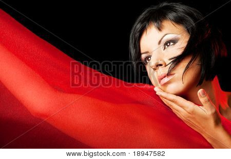 portrait of a young beautiful female with red semitransparent fabric