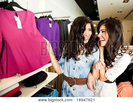 Beautiful smiling twin females at fashion boutique, looking at clothes