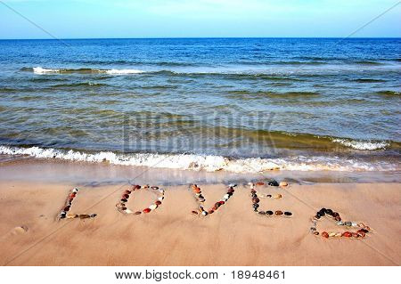 Word LOVE on beach sand, made from rocks